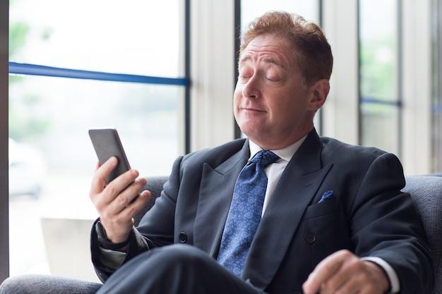 Maduras, homem negócios, usando, cellphone, levantamento, sobrancelhas