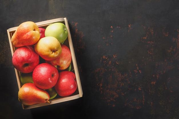Maduras maçãs verdes e vermelhas com peras em uma caixa de madeira no escuro.