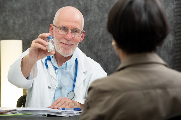 Maduro médico dando pílulas no seu paciente