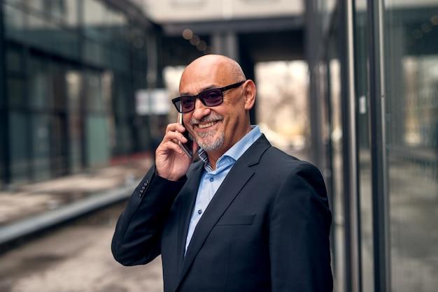 Maduro profissional elegante empresário alegre está falando ao telefone em pé na passagem da rua estreita.