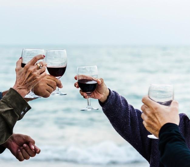 Maduros amigos bebendo vinho na praia