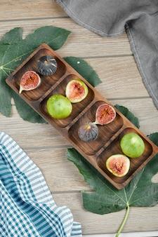 Maduros inteiros e fatias de figos verdes e pretos numa travessa de madeira com uma folha e uma toalha de mesa.