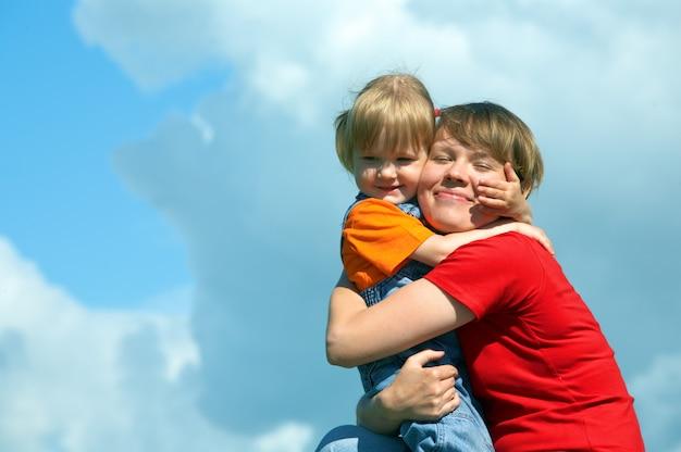 Mãe abraça a filhinha no céu azul