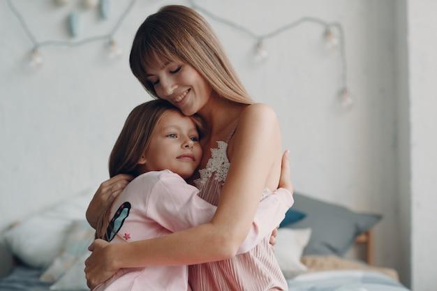 Mãe abraça com a filha pequena. fique em casa. perigo de coronavírus.