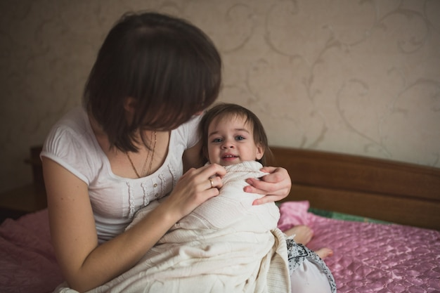Mãe abraça e brinca com a filha, esconde-esconde na cama, estilo de vida,