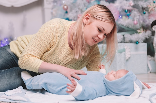 Mãe abraça seu bebê perto da árvore de natal. o conceito de natal