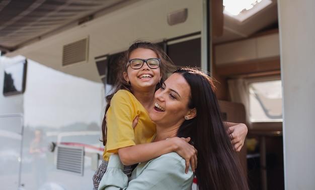 Mãe abraçando a filha de carro ao ar livre em acampamento ao entardecer, viagem de férias em família de caravana.