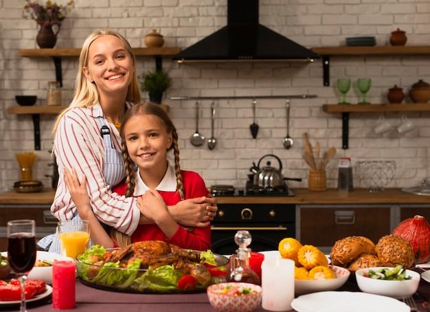 Mãe abraçando a filha na cozinha
