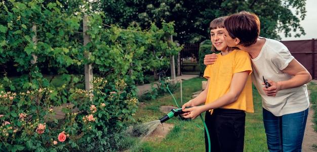 Mãe abraçando e beijando a filha enquanto ela rega o jardim