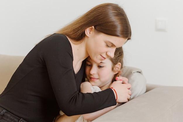 Mãe abraçando filha assustada