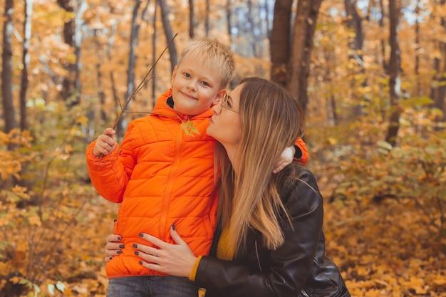 Mãe abraçando seu filho durante uma caminhada no outono parque outono e conceito de mãe solteira