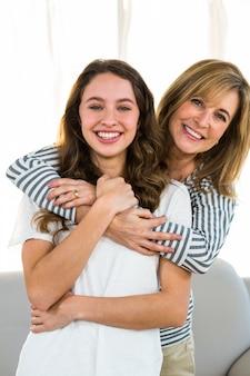 Mãe abraçar a filha dela e sorrindo para a câmera