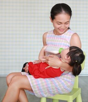 Mãe, abraçar, dela, cute, criança asiática, menina, bebendo, de, um, garrafa, em, a, sala de estar