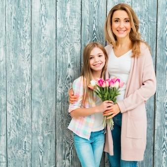 Mãe, abraçar, filha, e, segurando, tulips