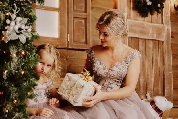 Mãe acalmando sua filha triste e chorando e dando a ela um presente em pé ao lado da árvore de natal