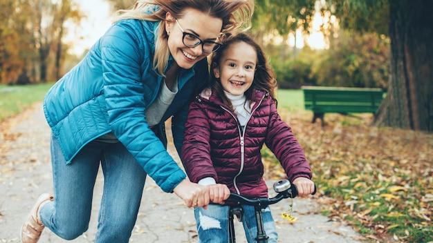 Mãe adorável com óculos tentando ensinar a filha a andar de bicicleta em um parque