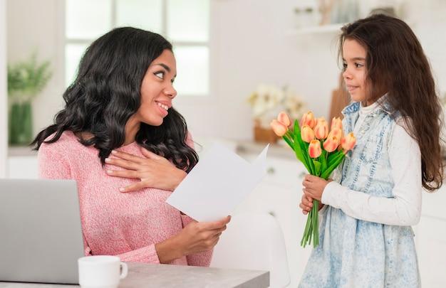 Mãe adorável garota surpreendente com flores