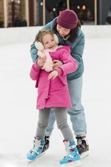 Mãe adorável que abraça a filha bonito