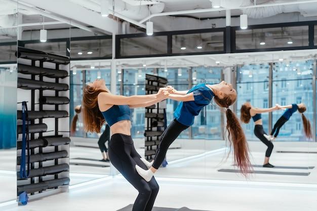 Mãe adulta jovem fazendo fitness com sua filha