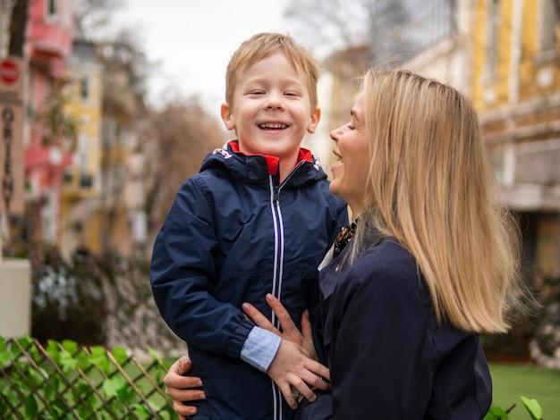 Mãe adulta, segurando o jovem rapaz ao ar livre
