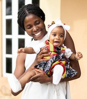 Mãe africana com tiro médio segurando uma garotinha