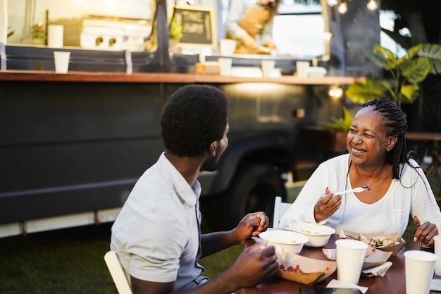 Mãe africana e filho comendo comida de caminhão de comida ao ar livre - família e conceito de verão - foco no rosto da mulher