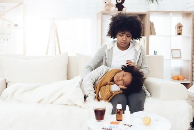 Mãe afro-americana com uma criança doente com gripe no colo.