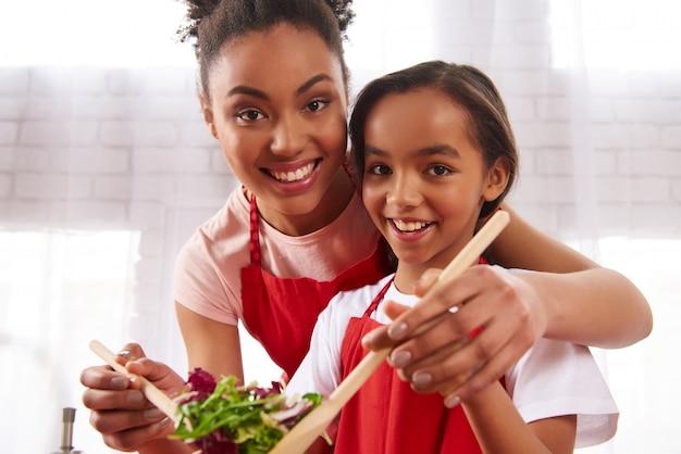 Mãe afro-americana e filha misturam salada