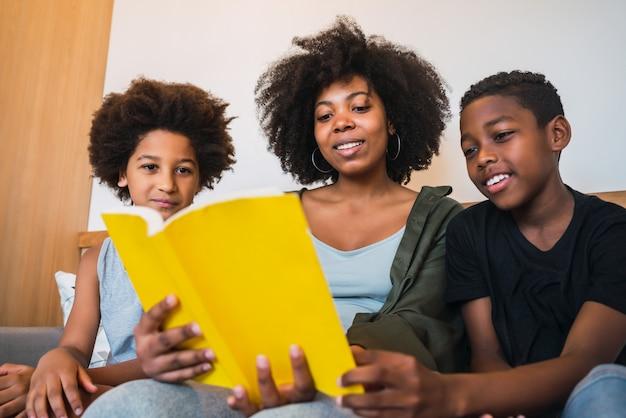 Mãe afro lendo um livro para os filhos.