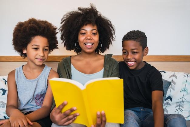 Mãe afro, lendo um livro para seus filhos.