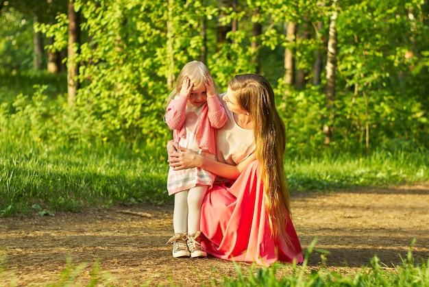 Mãe, agachada, pergunta à filhinha o que aconteceu, durante um passeio no parque