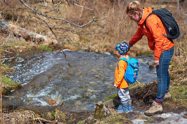 Mãe ajuda a criança a atravessar o fluxo através de um log. adulto ajuda a menina, leva pela mão. retrato ao ar livre ambulante