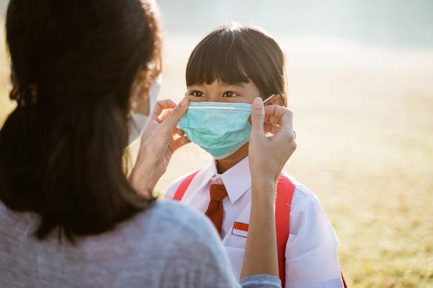 Mãe ajuda a filha a colocar a máscara antes de ir para a escola