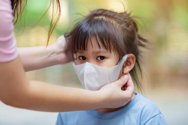 Mãe ajuda crianças usando a máscara para se proteger contra vírus e poluição do ar.