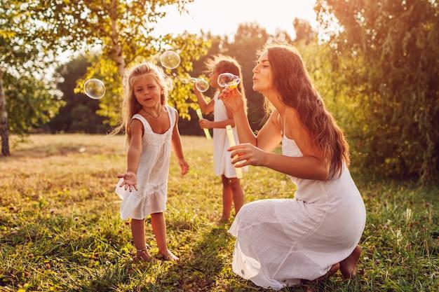 Mãe ajuda filhas a soprar bolhas no parque de verão