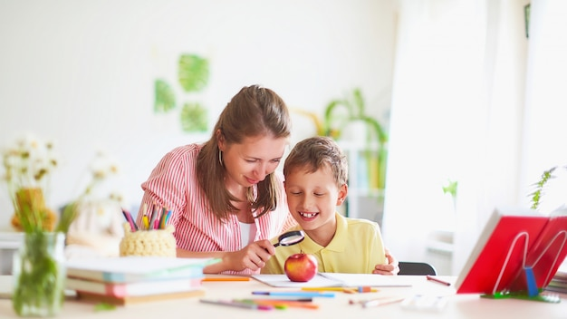 Mãe ajuda o filho a fazer a lição de casa.