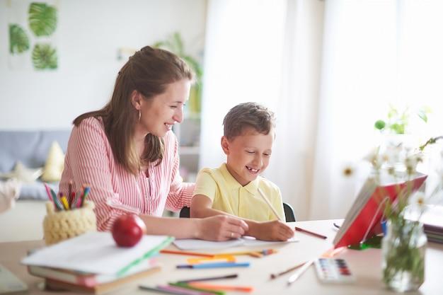 Mãe ajuda o filho a fazer aulas. educação escolar em casa