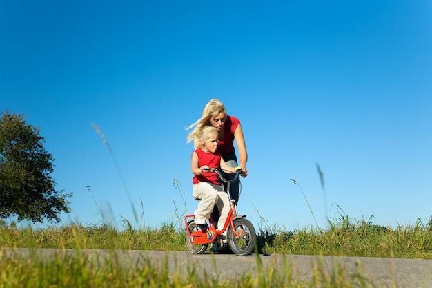 Mãe ajudando a filha a andar de bicicleta