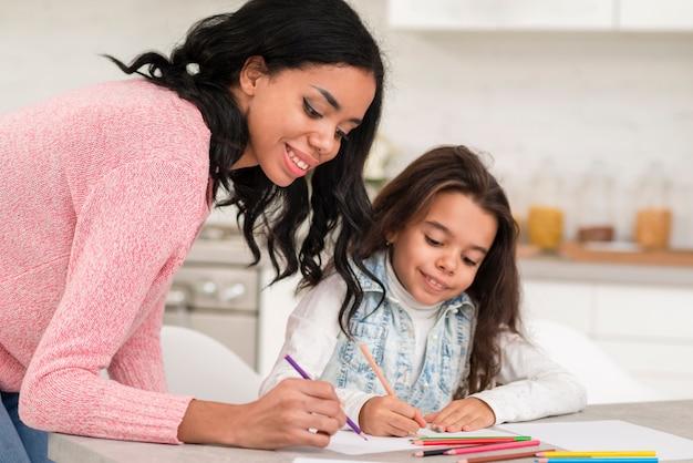 Mãe, ajudando a filha a colorir