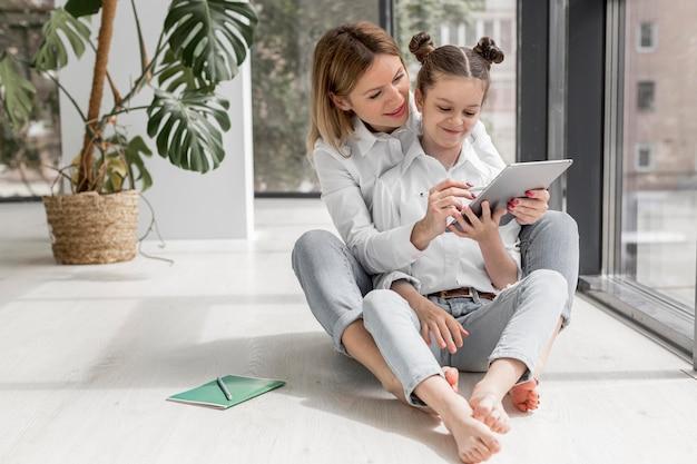 Mãe ajudando a filha a estudar dentro de casa