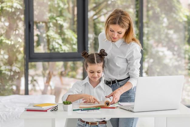 Mãe ajudando a filha a estudar