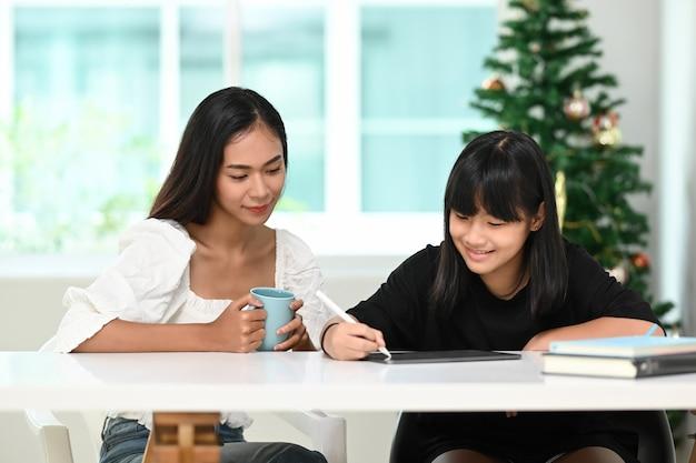 Mãe ajudando a filha a fazer a aula online de lição de casa no tablet digital em casa.