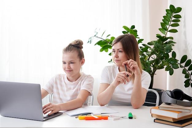 Mãe, ajudando a filha a fazer a lição de casa. o conceito de educação em casa em quarentena. diversão durante o ensino a distância