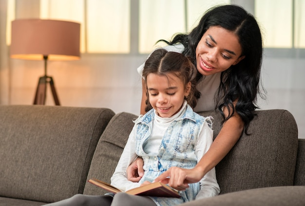 Mãe, ajudando a filha a ler