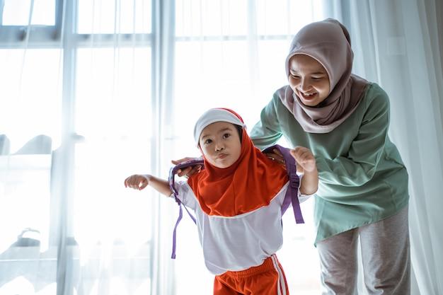 Mãe ajudando a filha a preparar a escola