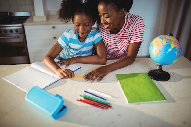 Mãe, ajudando a filha com a lição de casa