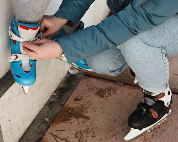 Mãe, ajudando a filha com patins de gelo