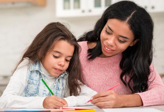 Mãe, ajudando a filha com trabalhos de casa