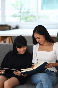 Mãe ajudando a filha dela fazendo lição de casa on-line tablet digital em casa. educação online.