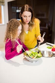 Mãe ajudando a filha em fazer salada